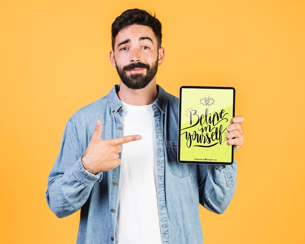Casual jeune homme pointant le doigt sur une tablette mock up Psd gratuit