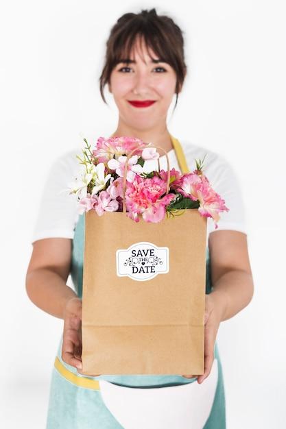 Concept de jardinage avec une femme tenant un sac avec des fleurs Psd gratuit