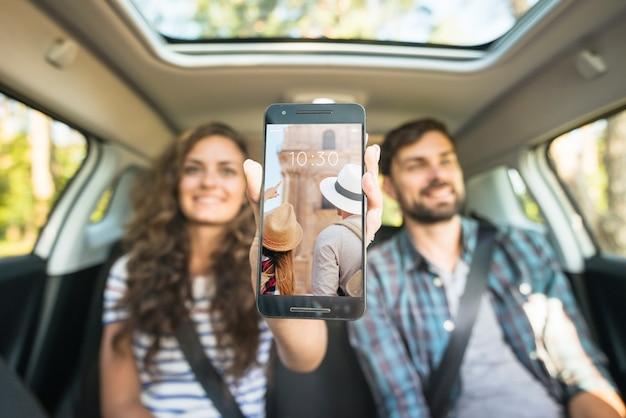 Couple dans la voiture montrant la maquette du smartphone Psd gratuit