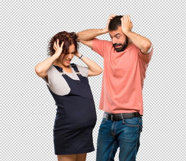 Couple avec femme enceinte prend les mains sur la tête car a la migraine PSD Premium
