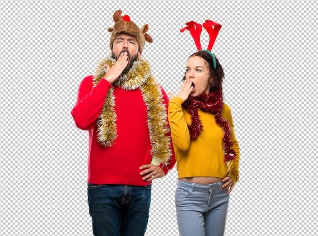 Couple habillé pour les vacances de noël bâillant et se couvrant la bouche avec la main. expression endormie PSD Premium