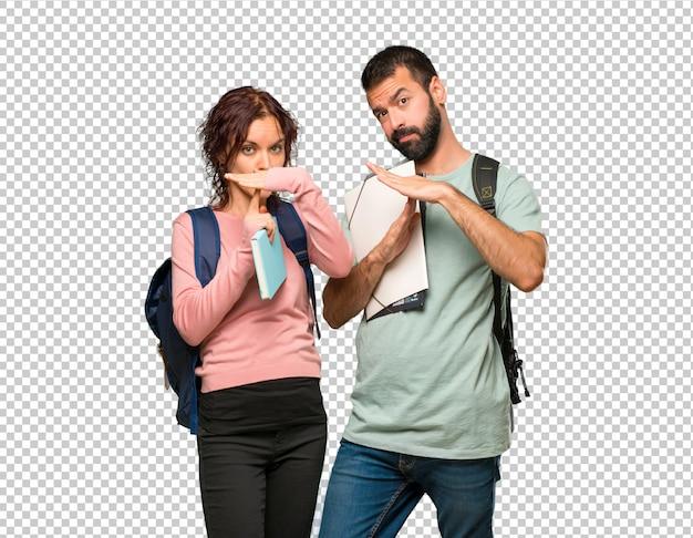 Deux étudiantes avec des sacs à dos et des livres faisant un geste d'arrêt de la main pour arrêter un acte PSD Premium