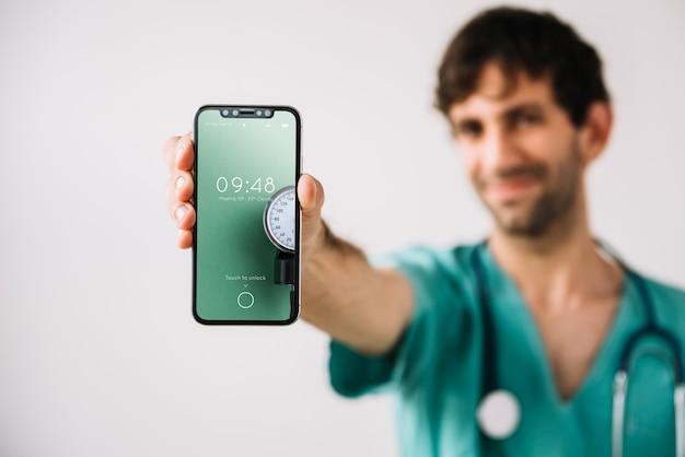 Docteur montrant la maquette d'un smartphone Psd gratuit