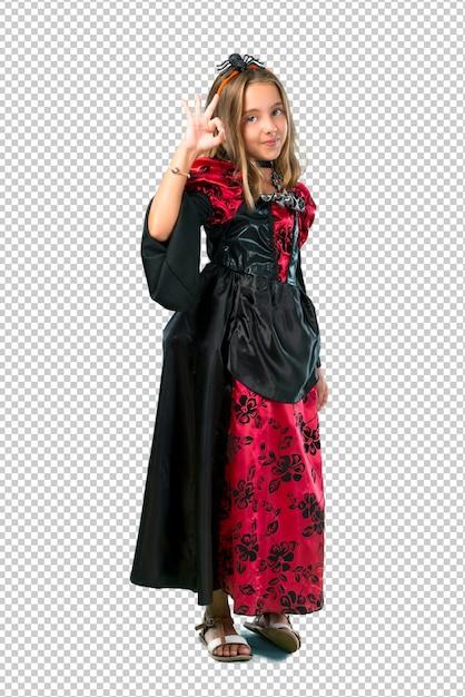 Enfant blonde habillée en vampire pour les vacances d'halloween montrant un signe ok avec les doigts PSD Premium