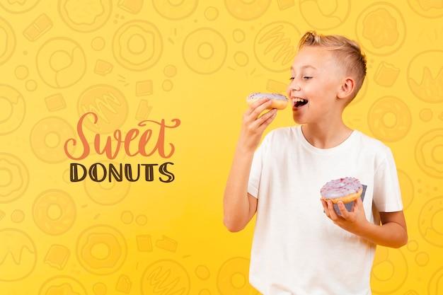 Enfant Heureux Mangeant Un Beignet Psd gratuit