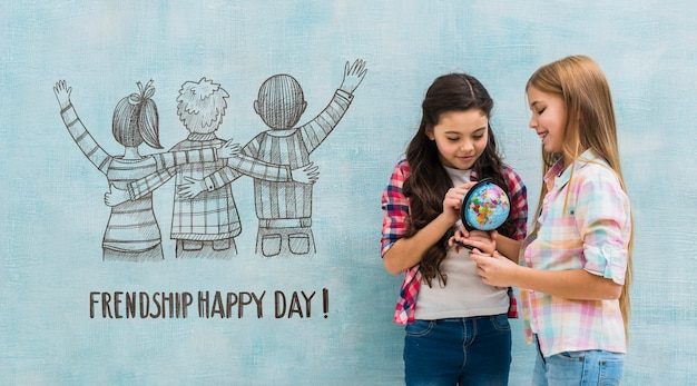 Enfants tenant un globe terrestre avec maquette du mur Psd gratuit