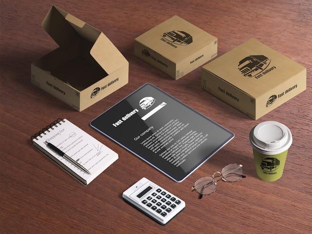 Ensemble d'articles de livraison, boîtes en carton, tablette, calculatrice, bloc-notes, tasse à café Psd gratuit