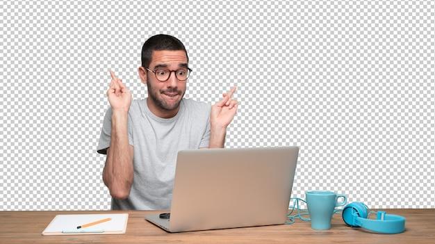 Espoir jeune homme assis à son bureau avec le geste des doigts croisés PSD Premium