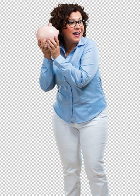 Femme d'âge moyen confiante et enjouée, tenant une banque de porcelets et se tais parce que l'argent est économisé. PSD Premium