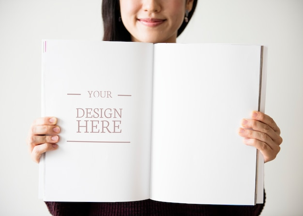 Une femme asiatique tient un magazine vierge PSD Premium