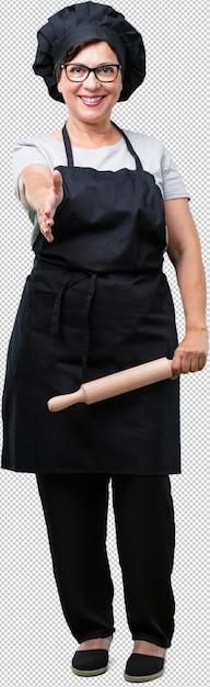 Femme de boulanger âgée moyenne du corps complet tendre la main pour saluer quelqu'un ou faire des gestes pour aider, heureux et excité PSD Premium