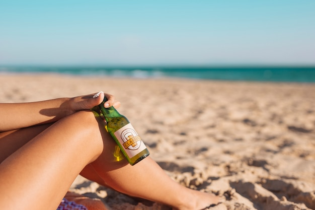 Femme, à, bouteille bière, maquette, plage Psd gratuit