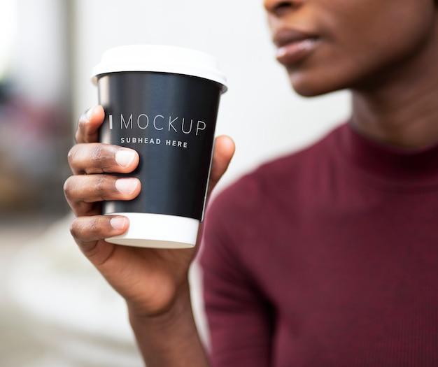 Femme buvant du café sur une maquette de tasse en papier PSD Premium