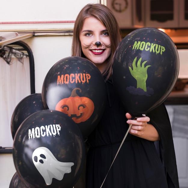 Femme En Costume D'halloween Tenant Des Ballons De Maquette Psd gratuit