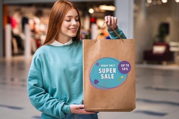 Femme dans un centre commercial tenant un grand sac en papier rempli de produits en vente Psd gratuit