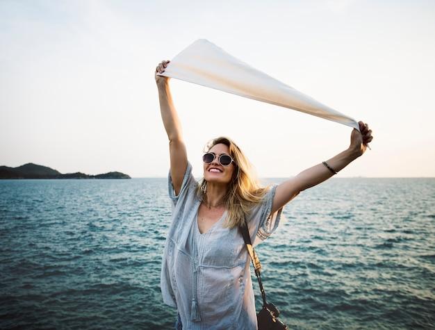 Femme devant la mer tenant le drapeau Psd gratuit