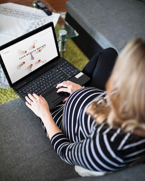 Femme enceinte sur le canapé à l'aide d'ordinateur Psd gratuit