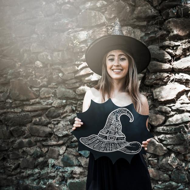 Femme, habillée comme une sorcière, tenant un croquis d'un chapeau Psd gratuit