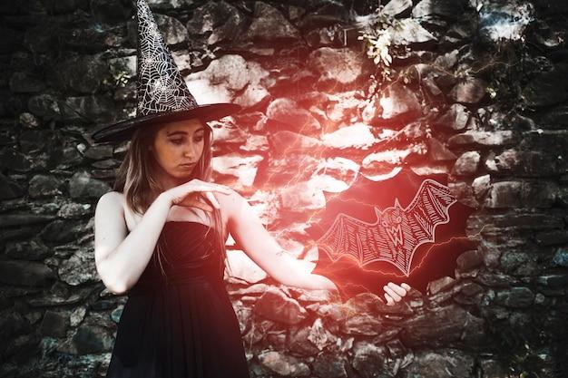 Femme habillée en sorcière faisant un sort de lumière rouge Psd gratuit