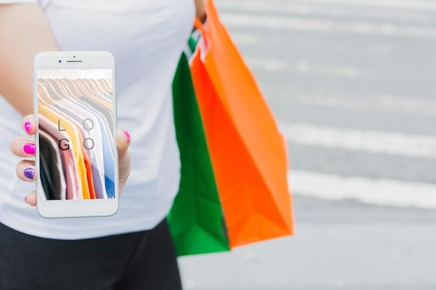 Femme avec maquette de smartphone et sacs à provisions Psd gratuit