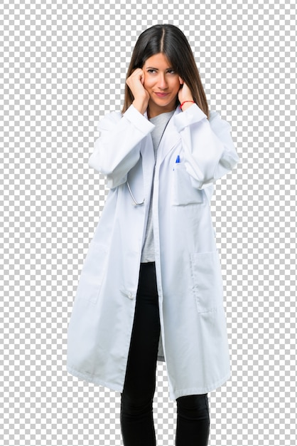 Femme médecin avec stéthoscope couvrant les deux oreilles avec les mains. expression frustrée PSD Premium