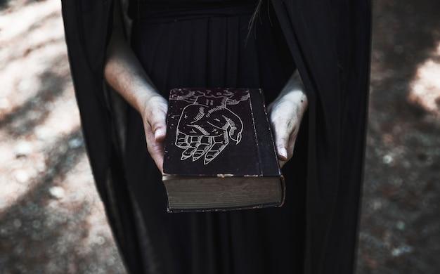 Femme montrant un livre fermé avec des sorts Psd gratuit