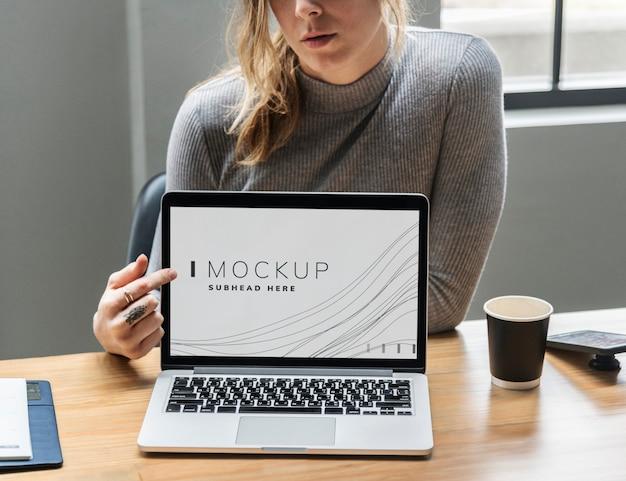 Femme montrant une maquette d'écran d'ordinateur portable PSD Premium