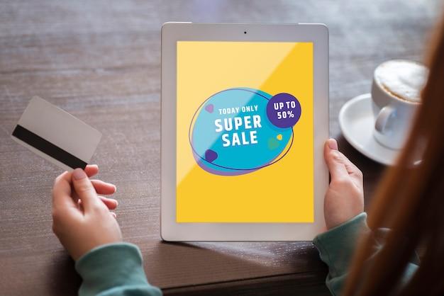 Femme regardant les ventes et détenant la carte de crédit Psd gratuit