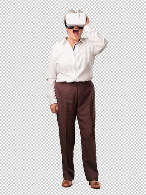 Femme senior pleine de corps, excitée et divertie, jouant avec des lunettes de réalité virtuelle, explorant un monde fantastique, essayant de toucher quelque chose PSD Premium