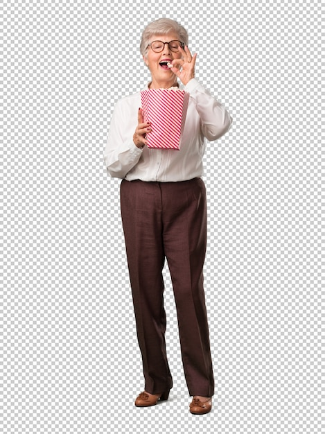 Femme senior pleine de corps, heureuse et fascinée, tenant un seau de maïs soufflé rayé, PSD Premium