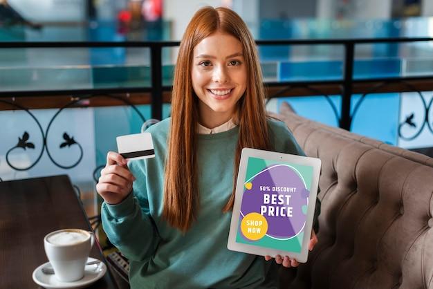 Femme souriante avec une carte de crédit et une tablette dans ses mains Psd gratuit