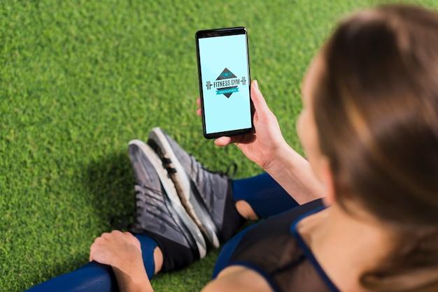 Femme sportive à l'aide de la maquette de smartphone Psd gratuit