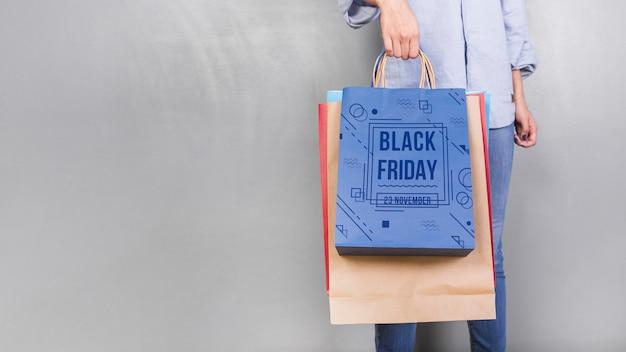 Femme tenant la maquette du sac de courses avec concept de vendredi noir Psd gratuit