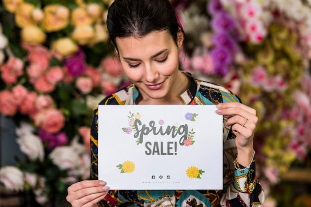 Femme tenant une maquette en papier pour la vente de printemps Psd gratuit