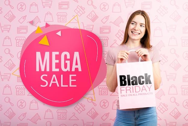 Femme tenant un sac en papier pour le vendredi noir Psd gratuit