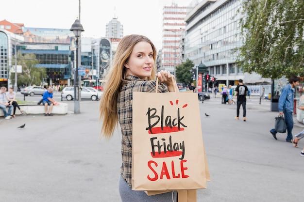 Femme en ville avec des sacs de vendredi noir Psd gratuit