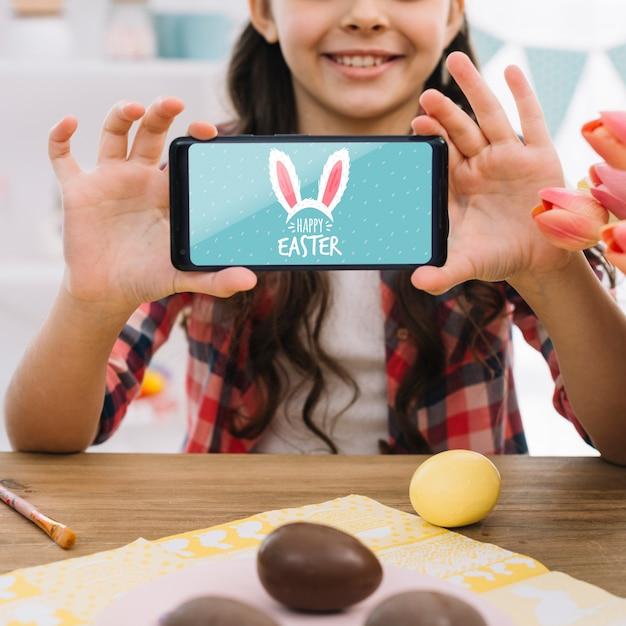 Fille avec une maquette de smartphone le jour de pâques Psd gratuit