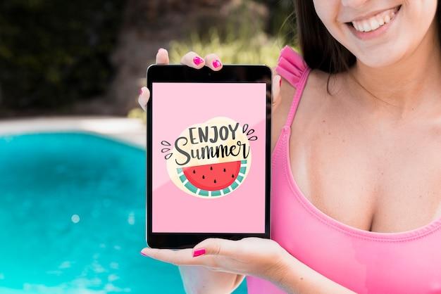 Fille présentant la maquette de la tablette à côté de la piscine Psd gratuit