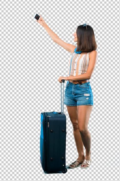 Fille voyageant avec sa valise prenant un selfie avec le mobile PSD Premium