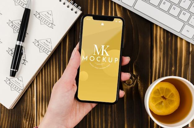 Flat Lay Hand Holding Smartphone Maquette Avec Du Thé Sur Le Bureau Psd gratuit