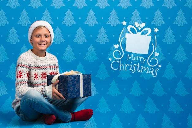 Garçon Vêtu De Cadeau D'ouverture De Pull Thématique De Noël Psd gratuit