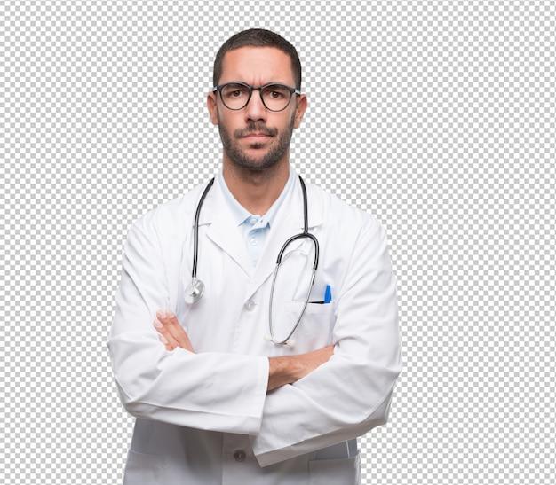 Grave jeune médecin avec geste des bras croisés PSD Premium