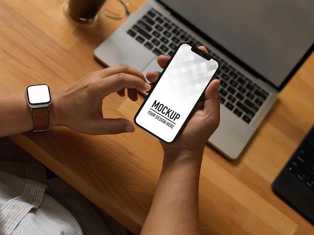 Gros Plan D'homme D'affaires à L'aide De Smartphone Sur Table De Travail Avec Ordinateur Portable Dans La Salle De Bureau à Domicile PSD Premium