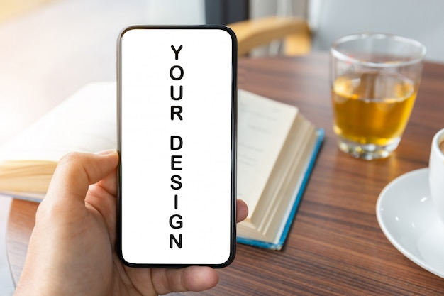 Gros plan de la main du jeune homme à l'aide d'un smartphone mobile avec livre flou et fond de tasse de tasse à café blanche, maquette. PSD Premium