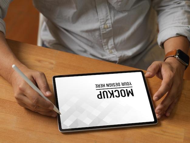 Gros Plan Des Mains Mâles à L'aide De Tablette De Maquette Numérique Sur Table En Bois PSD Premium