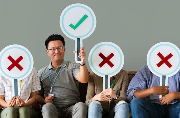 Groupe de personnes détenant des icônes vraies et fausses PSD Premium