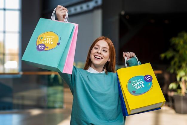 Heureuse femme soulevant ses sacs en papier dans un centre commercial Psd gratuit