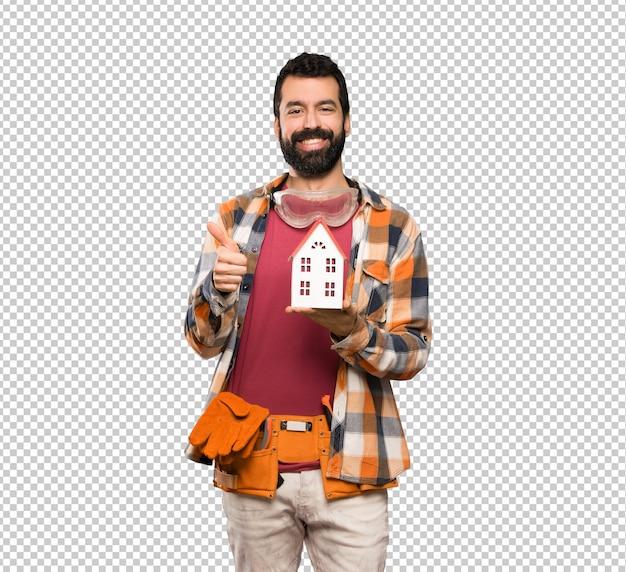 Heureux artisan homme tenant une petite maison PSD Premium