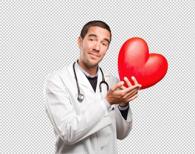 Heureux Docteur Tenant Un Coeur De Jouet Sur Fond Blanc PSD Premium