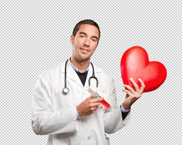Heureux Docteur Tenant Un Coeur De Jouet Et Une Seringue Sur Fond Blanc PSD Premium
